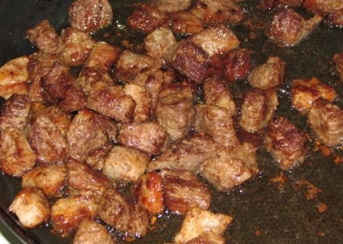 Разогреваем в сковороде масло и обжариваем мясо до румяной корочки.