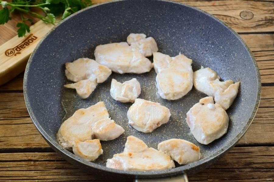 Обжарьте куриную грудку до легкого золотистого оттенка.