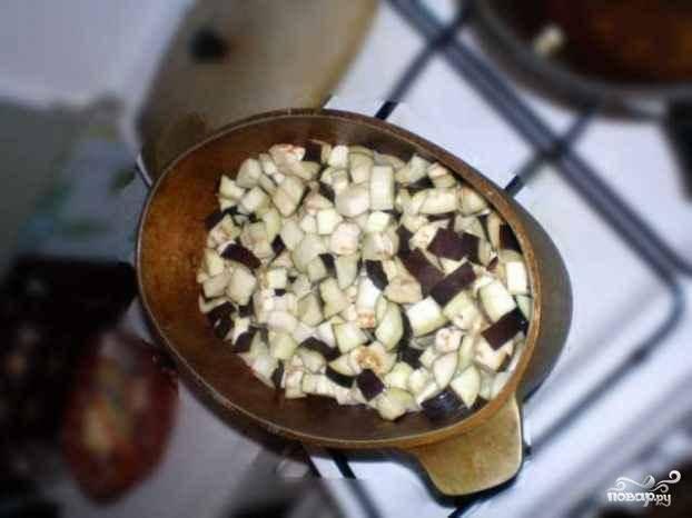 Следом добавляем лук и баклажаны. Тушим еще около 10 минут.