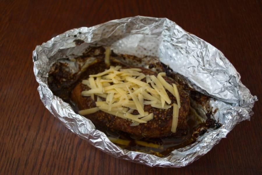 Из фольги сделайте лодочку. Поместите в нее нафаршированное филе. Остатки маринада вылить сверху. Разогреть духовку до 200 градусов. Запекать там мясо около 20 минут. Достать. Посыпать сыром и вернуть в духовку для плавки сыра.