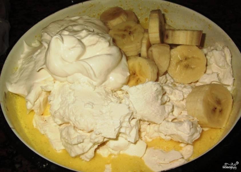 Взбейте яйца и оставшийся сахар. Соедините их с творогом и кусочками банана. Взбейте массу в блендере до единой консистенции или помните вилкой.