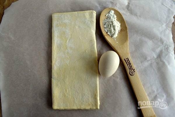 Тесто заранее достаньте из морозильника и разморозьте при комнатной температуре. Рабочую поверхность присыпьте немного мукой.