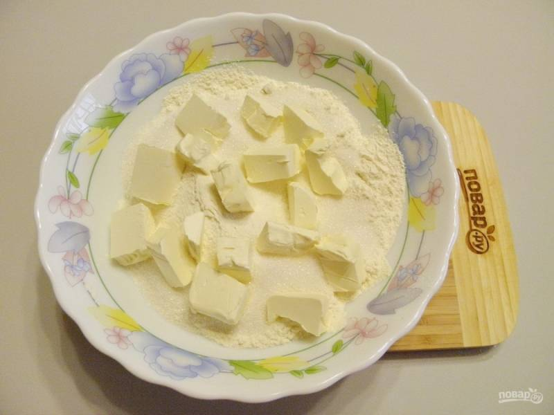 Смешайте муку с сахаром и разрыхлителем. Порежьте охлажденное сливочное масло кубиками, руками перетрите все в мелкую крошку.