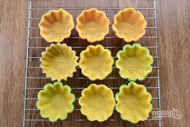Раскатайте каждую часть в тонкую лепешку, распределите их по силиконовым формочкам для кексиков. Наколите тесто вилкой и отправьте в запекаться в духовку при 200 °С на 20 минут.