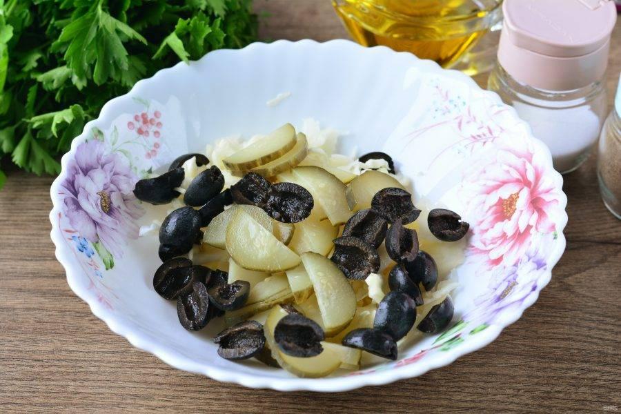 Переложите в миску все нарезанные ингредиенты: капусту, маслины и огурцы, перемешайте с чесноком, выдавленным через пресс. Чеснок добавляйте по вкусу.