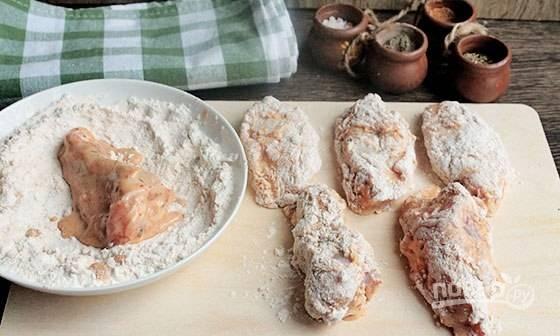 Сделайте панировку. Смешайте муку с паприкой и куркумой. Обваляйте в ней кусочки курицы.