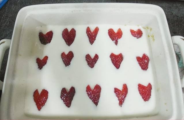 3. Клубнику моем и удаляем хвостики. Делаем у основания треугольные надрезы, чтобы ягоды стали напоминать сердечки. Выливаем белый крем на корж, добавим ягодки и отправим в холодильник застывать.