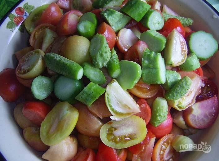 Овощи промойте под холодной. Томаты нарежьте четвертинками, а огурцы — дольками. Сложите все в широкую эмалированную посуду.