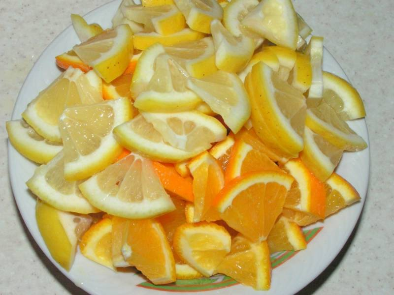 Нарезаем небольшими кусочками апельсины и лимоны и вытаскиваем косточки.