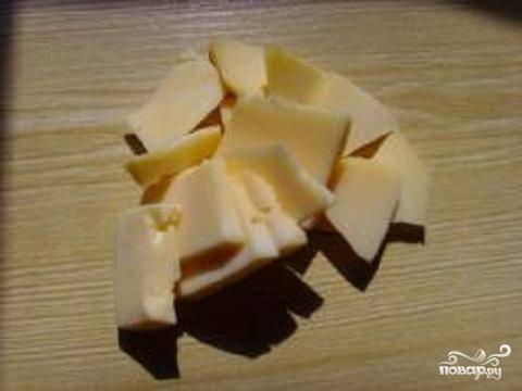 2.Твердый сыр нарезать тонкими квадратиками. Рассчитывайте по два кусочка сыра на одну ножку.  Ломтики засунуть в каждую ножку между кожицей и мясом.