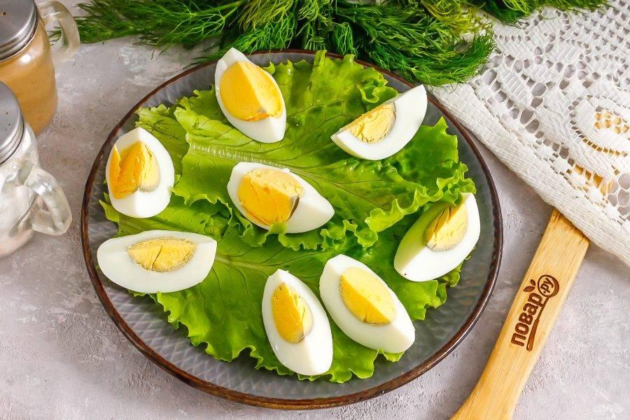 Промойте листья салата, стряхните с них лишнюю жидкость и выложите на тарелку. Очистите куриные яйца от скорлупы и промойте, нарежьте четвертинками и выложите на листья салата.