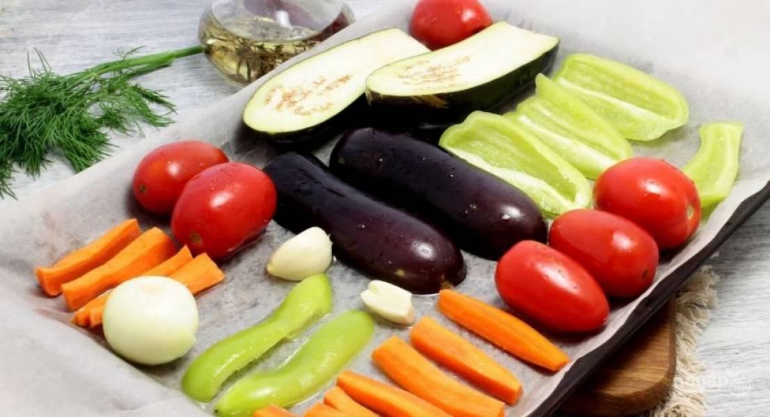 Овощи крупно нарежьте (кроме помидоров), которые необходимо почистить, и все промойте и обсушите. Разложите их на пергамент на противне и сбрызните маслом.