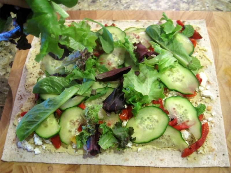 Вымойте и обсушите все овощи, огурец нарежьте тонкими кружками, перец — полосочками. Порежьте фету некрупно. Все ингредиенты для начинки разложите на хуммус. Посыпьте перцем по вкусу и сбрызните маслом.