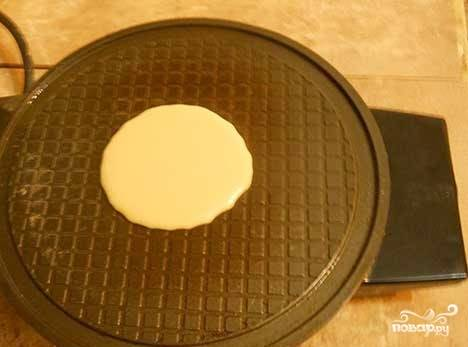 2. Наливаем немного теста на раскаленную основу вафельницы и выпекаем наши рожки. По такому же принципу готовятся и трубочки. Открыв крышку, нужно быстро завернуть рожок, пока он не застыл и не стал ломким.