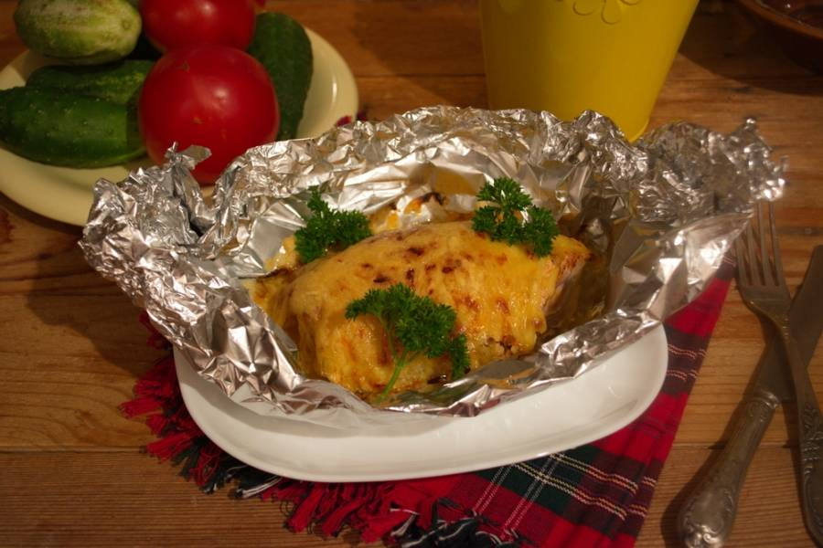 Натрите на терке твердый сыр. Выложите его поверх всего филе. Приподнимите края фольги и закрепите их в виде лодочки. Разогрейте духовку до 200 градусов. Запекайте филе в духовке около 40 минут.