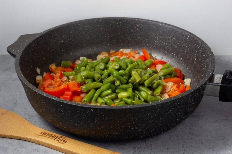 Перец немного обжарьте и добавьте фасоль. Жарьте всё вместе ещё 2-3 минуты.