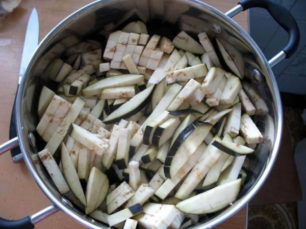 У баклажанов удаляем плодоножку, промываем их и нарезаем крупной соломкой. Выкладываем в кастрюлю так, чтобы баклажаны занимали не более 2/3 ее объема.