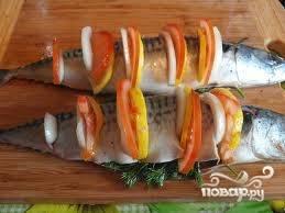 На спинке скумбрии сделайте неглубокие разрезы и вставьте кольца лука, помидора и лимона. Зеленью наполните брюшко рыбы.