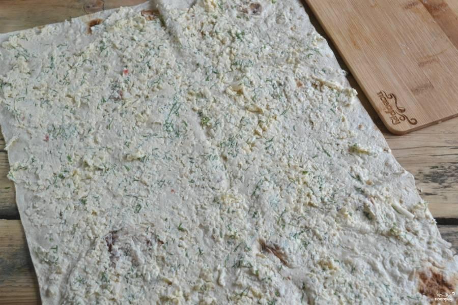 Ровным слоем намажьте сырную массу на лаваш, заверните его в рулет и оставьте минимум на 15 минут.