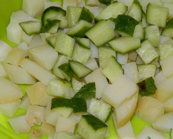 1. Яйца и картошку отварим. Из рыбы удаляем косточки. В миске смешаем картофель кубиками, свежие огурцы и отварные яйца.