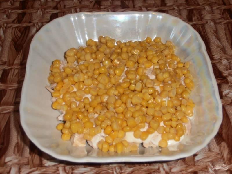 Слейте с консервированной кукурузы жидкость. Выложите чуть больше половины баночки кукурузы.