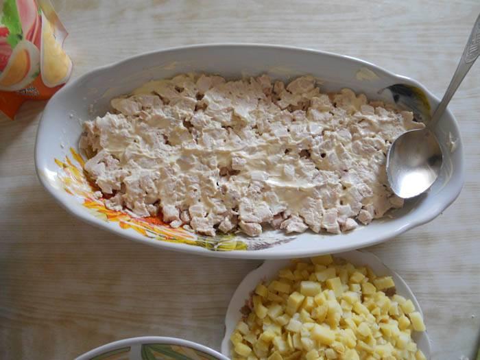 Затем начинаем укладку: слоями выкладываем курицу, картошку, грибы, лук. Все слоя смазываем майонезом.