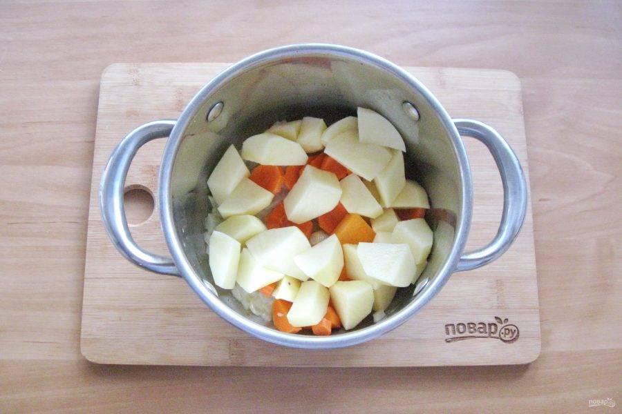 Картофель и морковь очистите и помойте, нарежьте кубиками. Добавьте в кастрюлю.