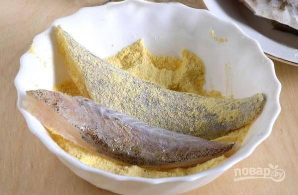 В небольшой посуде смешайте соль, черный молотый перец и кукурузную муку. Затем обваляйте в этой смеси размороженное филе минтая.