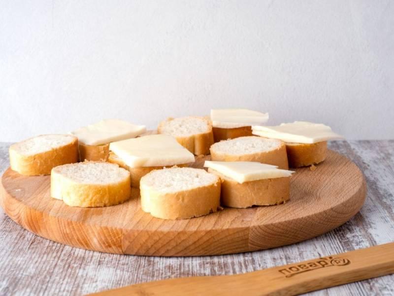 Багет нарежьте порционно кружочками. Для каждого бутерброда понадобится пара кружков багета. На один кусок выложите сыр.