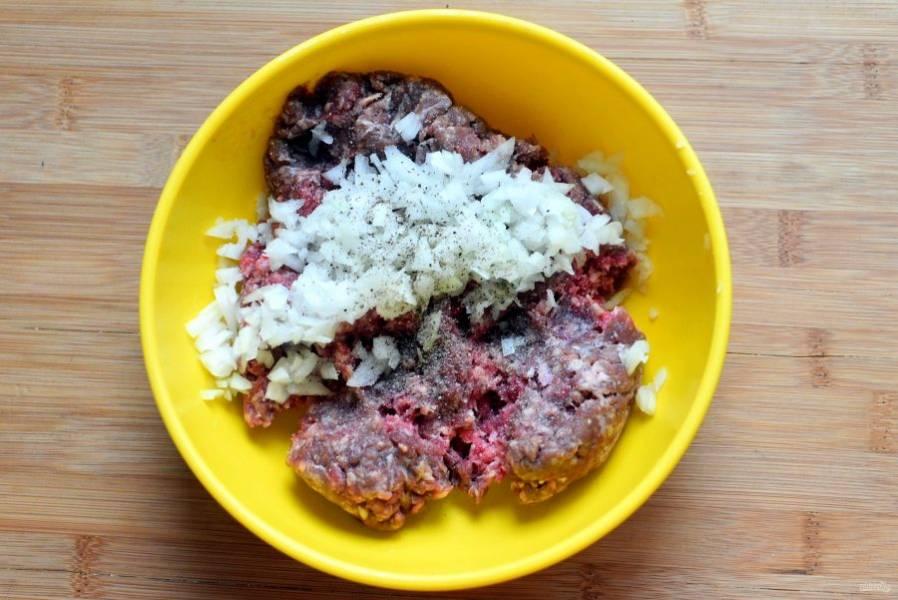 Соедините говяжий фарш с мелко нарубленным репчатым луком, посолите и поперчите по вкусу. Хорошо вымешайте и отбейте фарш.