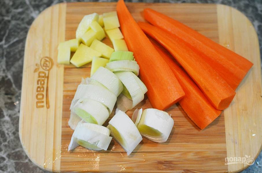4. Морковь очистите и нарежьте вдоль, сельдерей нарежьте ломтиками, а лук-порей — кольцами.