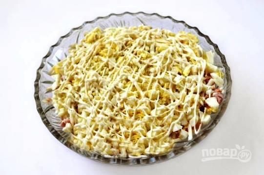 Очищенные от скорлупы вареные яйца тоже нарезаем мелкими кубиками. Делаем слой из половины порции. И снова сетка из майонеза.