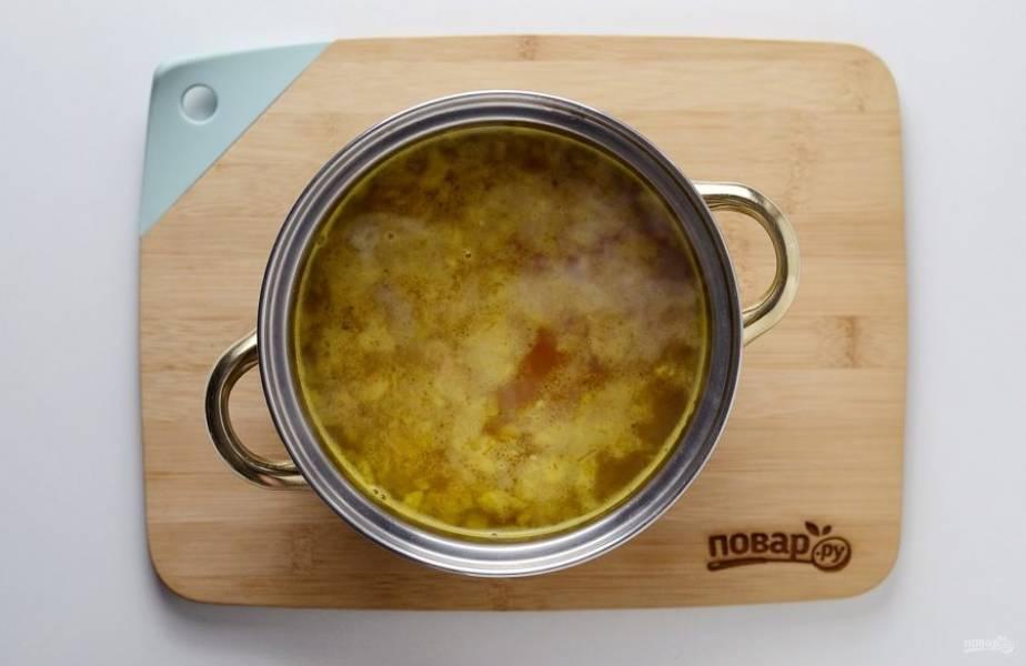 Переложите зажарку в кастрюлю. Влейте овощной бульон, посолите и доведите до кипения.