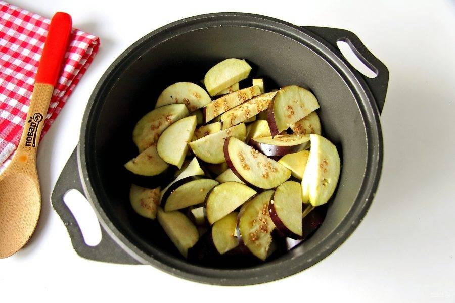 Баклажаны нарежьте кружочками, толщиной примерно 1 см. Затем каждый кружок разрежьте еще пополам. Сложите баклажаны в любую подходящую посуду с толстым дном.