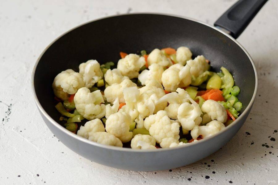 Добавьте цветную капусту. Приправьте перцем и солью. Прогрейте еще одну минуту.