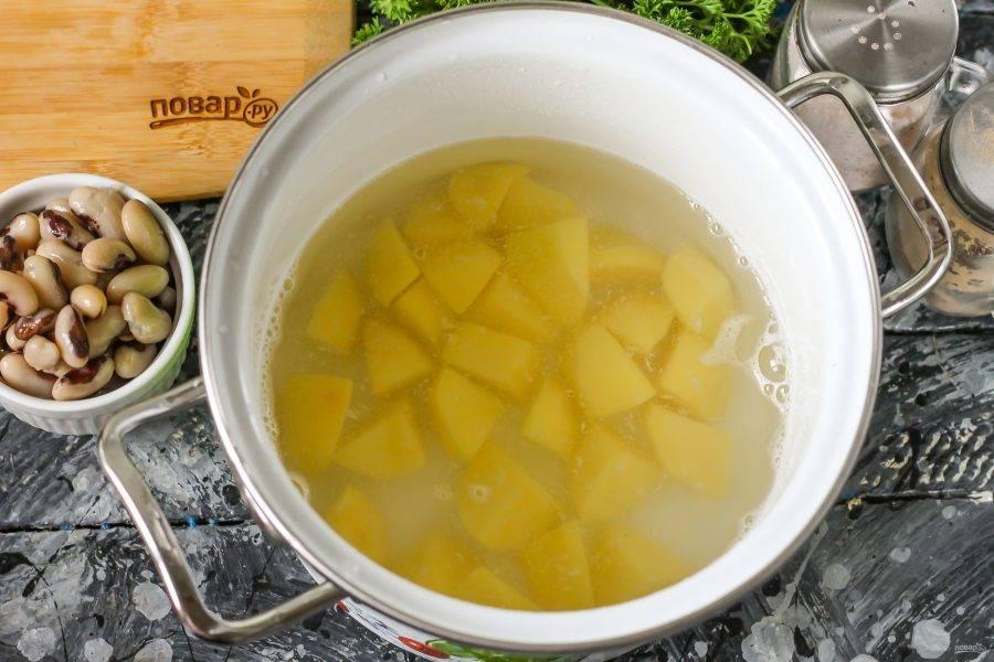 Картофель очистите от кожуры, промойте в воде и нарежьте средними кубиками. Выложите в кастрюлю, залейте теплой водой и отварите в течение 15 минут.