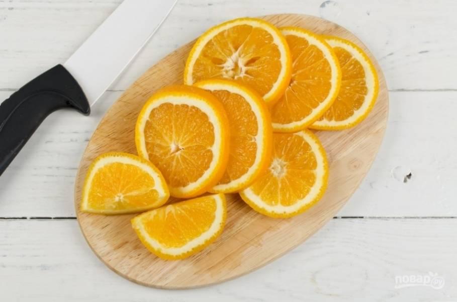 Апельсины промойте. Нарежьте меньшую часть дольками, а большую — кольцами.