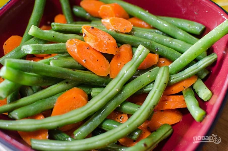 3. Морковь нарежьте толстыми кружками, фасоль — половинками. Перемешайте овощи с солью и перцем, также добавьте немного чеснока.