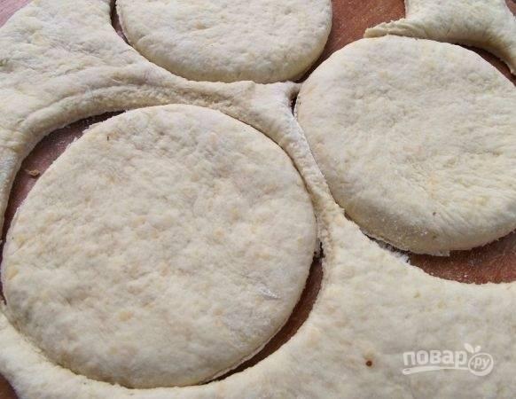 4. Раскатайте тесто, но не очень тонко. Вырежьте кружочки и переложите их на противень, застеленный пергаментом. Духовку разогрейте до 170 градусов.