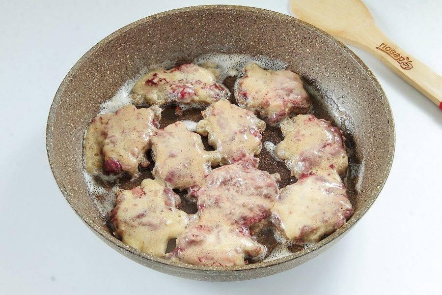 Окунуть кусочки печени в кляр и выложить на разогретую с маслом сковороду.