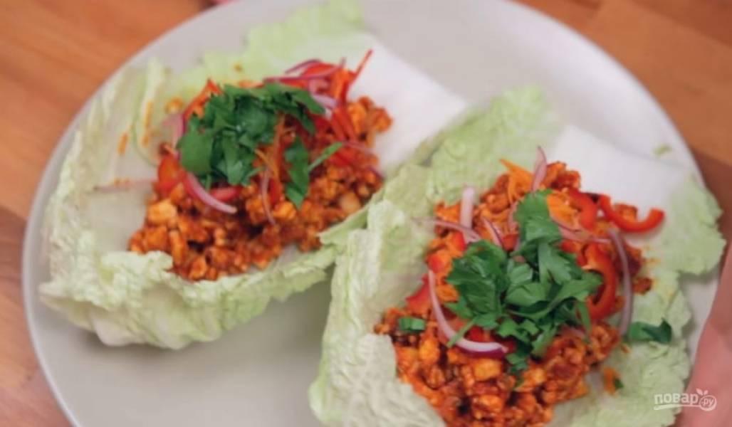 3. Выберите листья капусты, которые похожи на чашечки, и выложите в них обжаренную курицу. Нарежьте еще немного овощей. У меня это красный сладкий перец, лук и морковь. Украсьте ими чашечки.