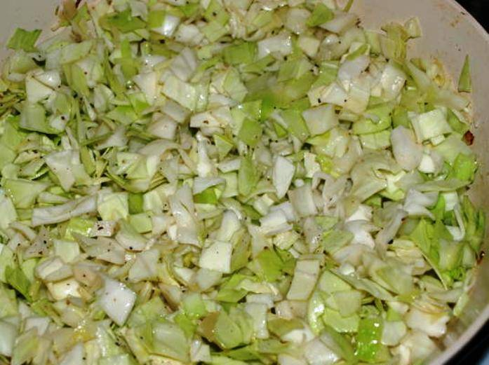 Обжарьте лук на сковороде, добавьте мелко пошинкованую капусту и слегка протушите в течение 10 минут под крышкой. Орехи потолките в ступке и смешайте с капустой. Добавьте соль и чабрец.