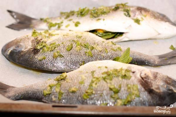 Получившимся маринадом обильно смазываем нашу рыбу. Внутрь каждой рыбы кладем по ломтику лимона и по веточке свежей мяты.