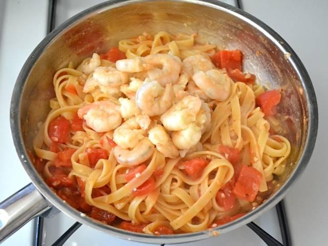 6. Затем добавьте в сковороду готовую пасту, предварительно слив воду. Немного воды, в которой варилась паста, можно оставить и добавить в сковороду, если блюдо покажется вам сухим. Туда же идут креветки. Снова все перемешиваем.