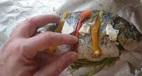 Рыбу выложить на фольгу на зелень, натереть чесноком, уложить кусочки масла, в прорези перец.