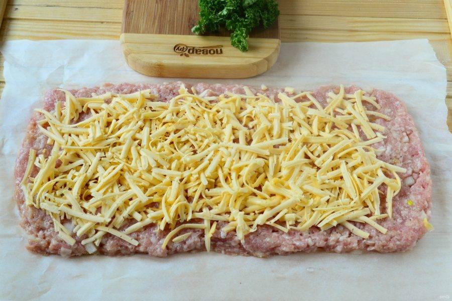 Твердый сыр натрите на крупной терке и выложите ровным слоем на фарш.
