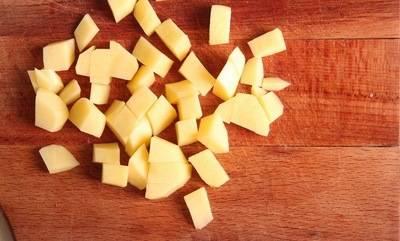 Картофель режем кубиками и отправляем в бульон.