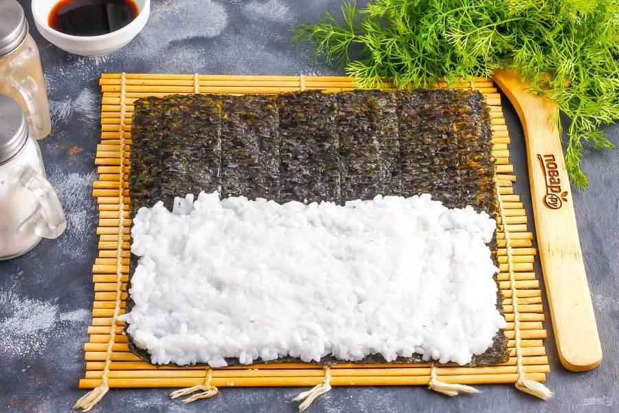 Рис остудите примерно 20-30 минут. На коврик выложите лист нори шершавой стороной наверх, гладкой — вниз. Выложите на нори рис, стараясь заполнить часть листа, оставляя сверху полосу в 2-3 см. незаполненной. Плотно прижмите рис, но не делайте слишком толстый слой, иначе у вас будет много риса в роллах.