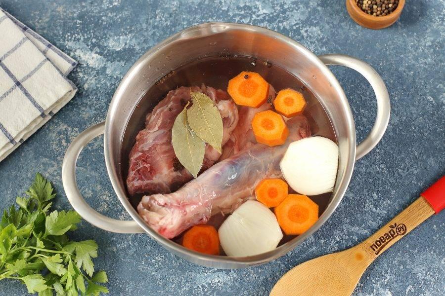 В кастрюлю выложите промытое мясо. Добавьте лавровый лист, перец горошком, соль по вкусу, одну нарезанную морковь и луковицу. Варите до полной готовности мяса. Готовый бульон необходимо затем процедить, а мясо отделить от костей и нарезать кусочками.
