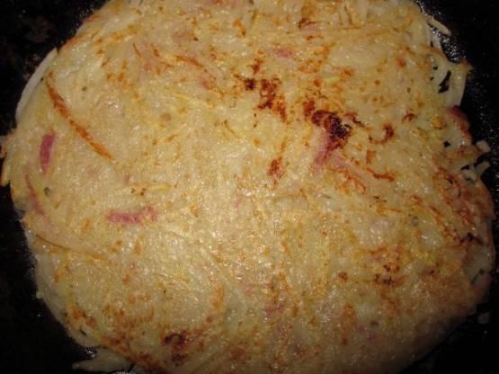 Затем картофельный блин переворачиваем и еще немного обжариваем.